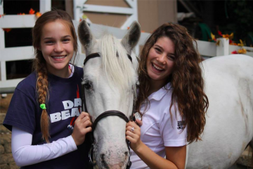 Two girls and a white horse.